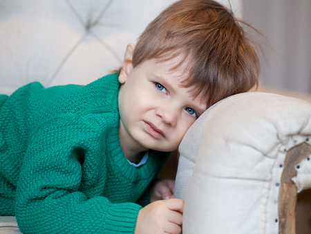 disgruntled: Suspicious boy lies on the couch Stock Photo
