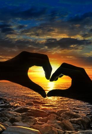 tocar las manos en forma de corazón, y el atardecer