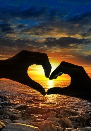 touching hands in a heart-shaped and sunset Stock Photo - 12653164