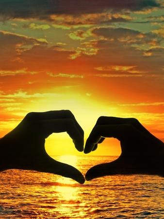 man vrouw symbool: handen en zonsondergang boven zee