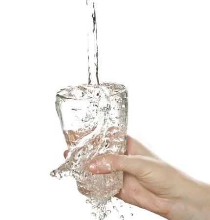 ženská ruka držící sklenici vody