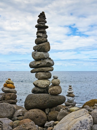 high stack of pebbles on the beach and sea background photo