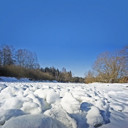 snow covered river and blue sky photo