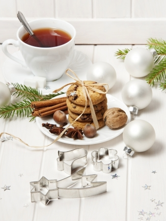 christmas still life with biscuits and a cut of tea on white wooden background photo