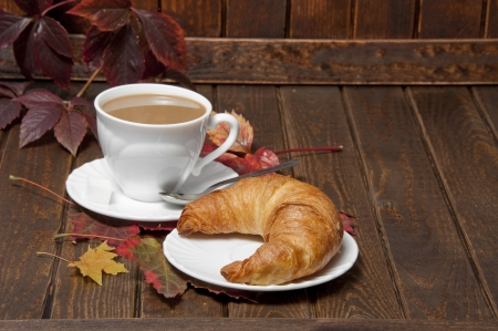 a croissant and a cup of coffeee with milk on a old wooden table photo
