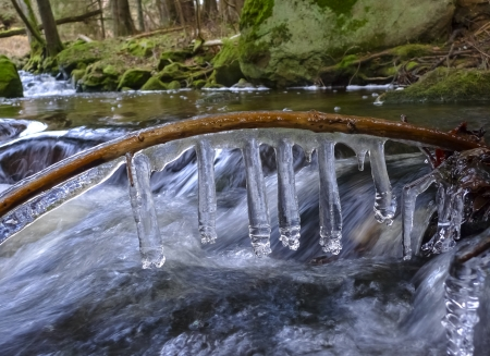 winter thaw: a brook with icicles - early spring