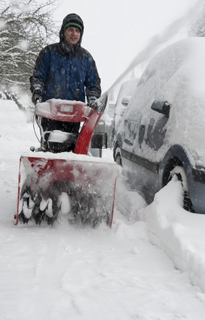 man working with a snow blowing machine on the street photo