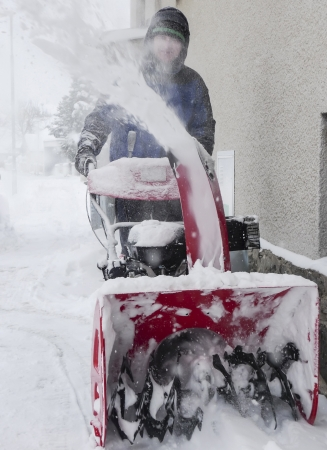 snow drift: a man working with a snow blowing machine on the street Stock Photo