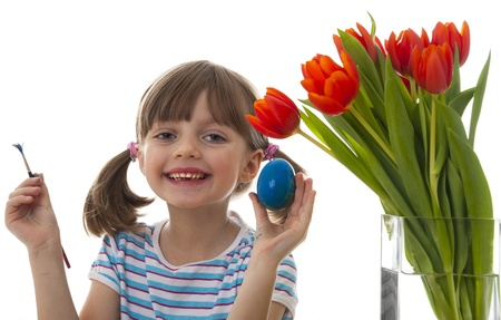 happy little girl coloring easter eggs photo