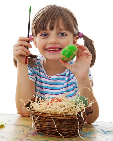 a happy little girl painting easter eggs - white background photo