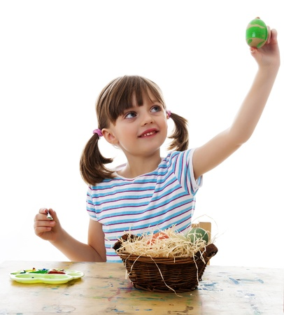 little girl coloring easter eggs  - white background photo