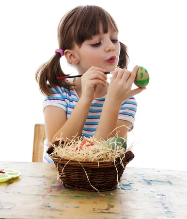 little girl coloring easter eggs white background photo