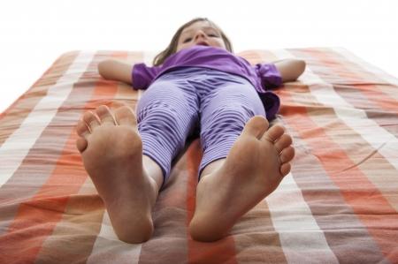ni�os contentos: ni�a acostada en una cama - descalzo