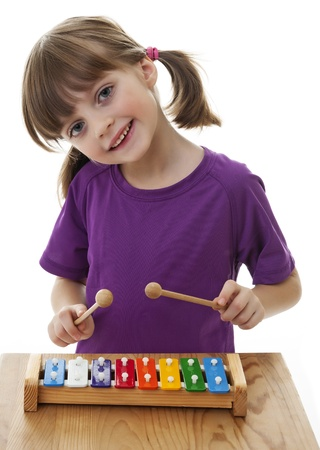 xilofono: ni�a jugando xil�fono - aislados en un fondo blanco