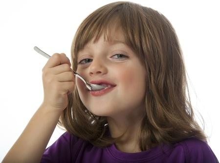 liten flicka äter en yoghurt närbild Stockfoto