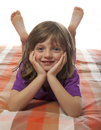 little girl lying on a bed photo