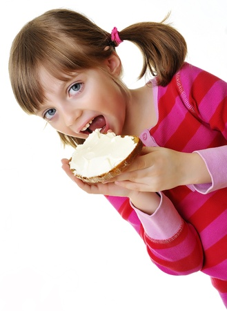 little girl eating a bread with cheese photo