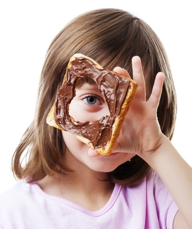 little girl looking through  bread with chocolate  butter photo