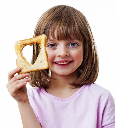 liten flicka som håller bröd på vit bakgrund Stockfoto