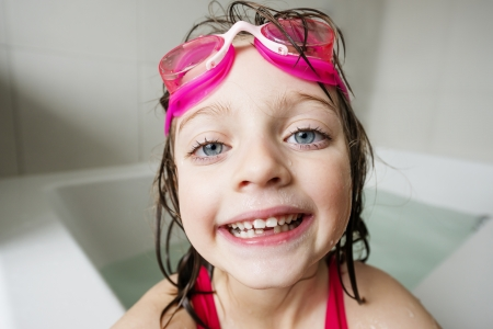 portrait of a happy  little girl with swim glasses bathing photo