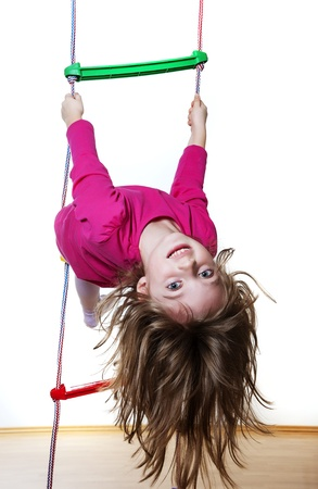 climbing sport: happy little girl climbing on a ladder at home