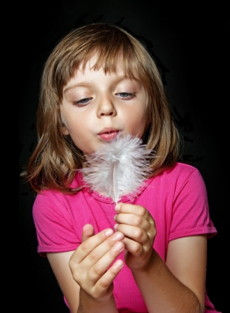 little girl blowing into white feather on dark background photo
