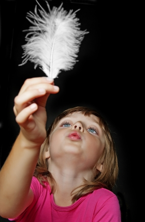 little girl blowing into white feather on black background photo