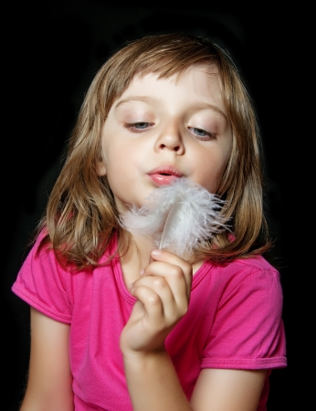 little girl blowing white feather on black background photo