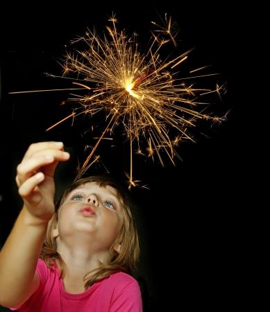 look pleased: little girl holding firewors on black background Stock Photo