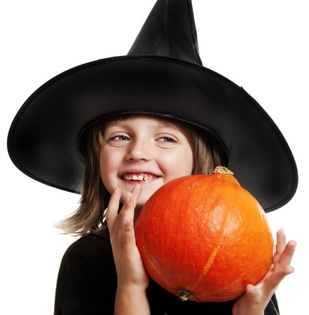 funy: little witch holding a pumpkin on halloween time