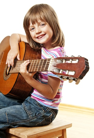little girl playing classical guitar photo