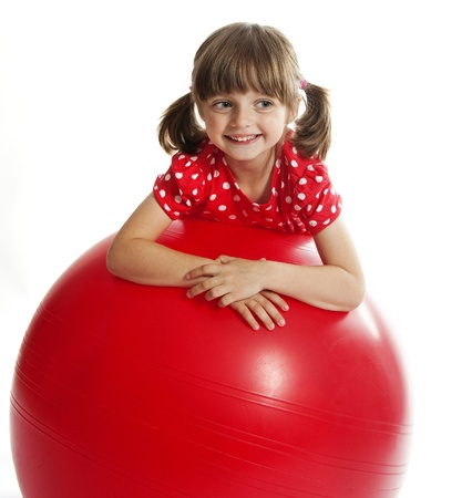 little girl doing fitness exercise with a red ball photo