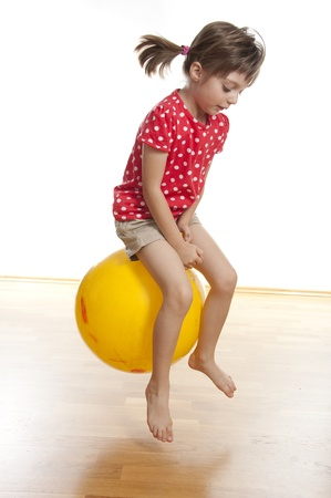 ball stretching: little girl jumping on ball Stock Photo