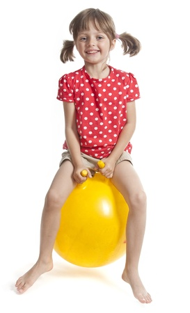 little girl jumping on ball - isolated photo