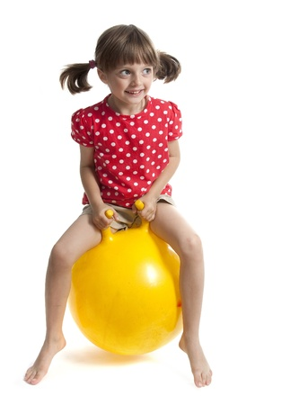 little girl jumping on ball - isolated on white photo