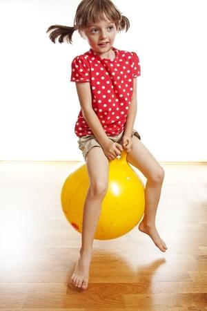 little girl jumping on yellow ball photo