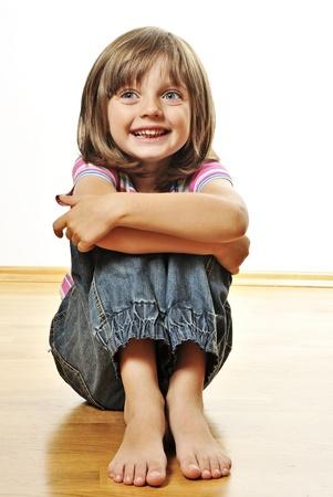 liten flicka sitter på ett trägolv - vit bakgrund Stockfoto