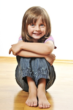 little girl barefoot: happy little girl sitting on a wooden floor