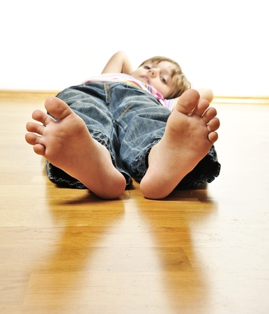 little girl barefoot: little girl resting on a wooden floor