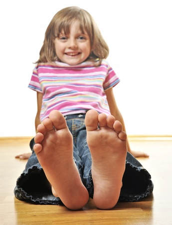 little girl barefoot: little girl sitting on a wooden floor