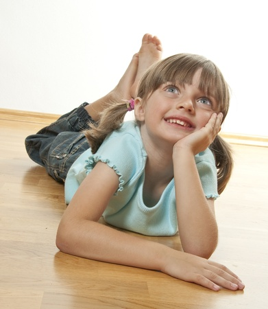happy little girl resting on a wooden floor photo