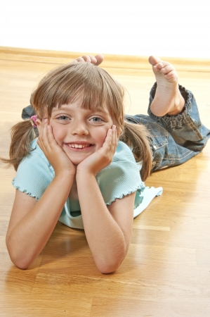 little girl resting on a wooden floor at home photo