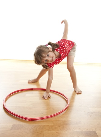 aerobic treatment: little girl doing fitness exercise with a hoop Stock Photo