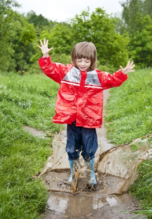 waterproof cape: happy little girl jumps in the pool - playing Stock Photo