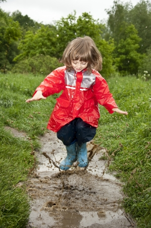 waterproof cape: happy little girl jumps in the pool  Stock Photo