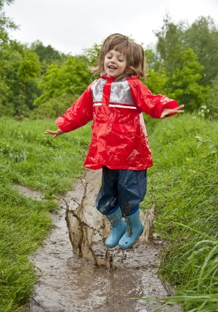 waterproof cape: little girl jumps in the pool