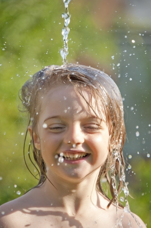 little girl playing with water - portrait photo