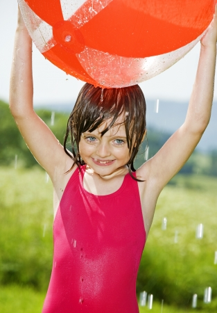 little girl swimsuit: little girl having fun with ball and rain of water dops
