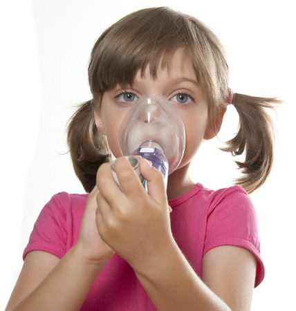 inhalation: ill little girl using inhaler - respiratory problems white background Stock Photo