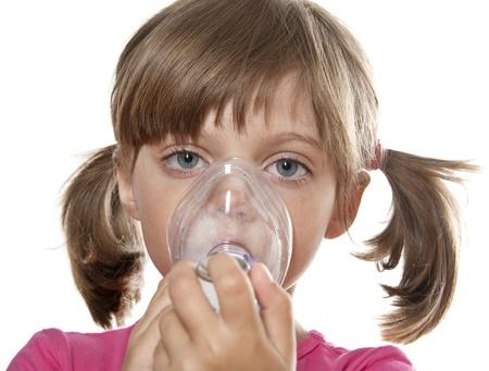 little girl using inhaler - respiratory problems photo